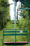 Vintage Ski Lift in Summer. An old two person chairlift in Northern Minnesota with dense forest and blooming wildflowers Royalty Free Stock Image