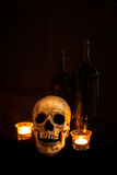 Vintage Skull and Wine by Candlelight. A vintage skull sits beside two wine bottles; image lit by candlelight and using a light painting technique stock photo