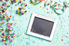 Vintage slate carnival or party background. With multicored twirled streamers and scattered confetti, copy space on the chalkboard viewed from above Stock Images