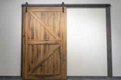 Vintage sliding door with open ferrous metal fittings. Wooden door stock images