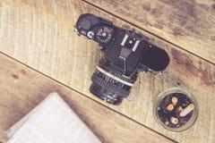 Vintage SLR camera ashtray newspaper on wooden table. Top view Vintage SLR camera ashtray newspaper on wooden table Stock Photo