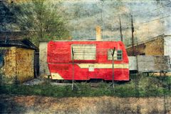 Vintage Small Red Camper Trailer and Clothesline. Vintage small red camper trailer sitting next to an alleyway. A clothesline sits out front with a brick chimney royalty free stock photography