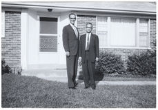 Vintage Snapshot: Tall man short man outside surburban house. Vintage Snapshot of two men, perhaps brothers, one very tall. Posing outside a suburban US home Royalty Free Stock Image