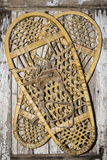 Vintage snow shoes on painted wood Stock Photos