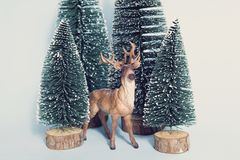 Vintage snowy forest firs and reindeer Stock Photo
