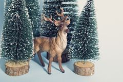 Vintage snowy forest firs and reindeer Stock Image