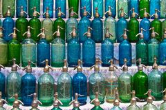 Vintage soda bottles for sale at Buenos Aires market. Vintage glass soda bottles in blues and greens are lined up on shelves at a street market in Buenos Aires Royalty Free Stock Photo