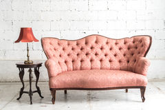 Vintage sofa and lamp on white wall. Pink vintage sofa and lamp on white wall Stock Photo