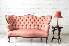 Vintage sofa and lamp on white wall. Pink vintage sofa and lamp on white wall Royalty Free Stock Photos