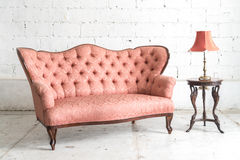 Vintage sofa and lamp on white wall. Pink vintage sofa and lamp on white wall Stock Photography