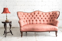 Vintage sofa and lamp on white wall. Pink vintage sofa and lamp on white wall Stock Photos