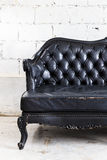 Vintage sofa on white wall. Royalty Free Stock Photography