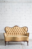 Vintage sofa on white wall. Stock Photos