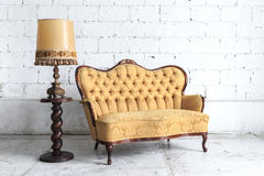 Vintage sofa on white wall. Royalty Free Stock Images