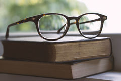 Vintage spectacles on books next to a window Stock Photos