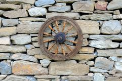 Vintage Spinning Wheel on Stone Wall Royalty Free Stock Photo
