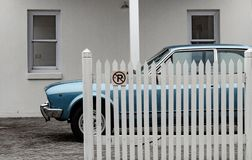 Vintage spirts car parked behind white fence; retro mood royalty free stock photos