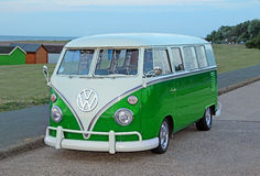 Vintage split screen volkswagon. Photo of a vintage split screen volkswagon parked up along coastal kerb in whitstable kent with beach huts in background.photo stock photos