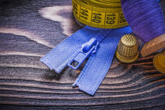 Vintage spool of thread measuring tape thimbles zip fastener on. Wooden board needlework concept stock photos