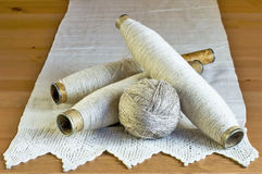 Vintage spools with natural linen threads and handmade lace  tablecloth on a wooden background. Stock Photos
