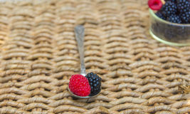 Vintage spoon and blackberries background. Blackberry on vintage metal spoon over wicker background Stock Images