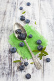 Vintage spoon with blueberries on white wooden table Royalty Free Stock Images