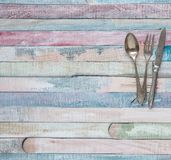 Vintage spoon, fork and knife on the background of the old colored boards stock image