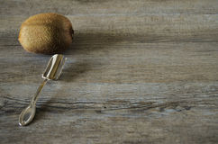 Vintage spoon and a kiwi. Vintage spoon on old wooden table, country style in low natural light with a brown kiwi Stock Photography