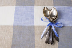 Vintage spoons on checkered tablecloth as background. Old spoons on table for country restaurant menu Stock Photography