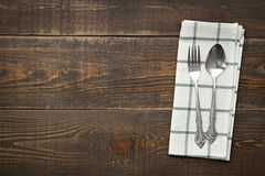Vintage spoons and fork with napery on wooden background. Royalty Free Stock Image