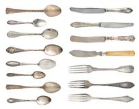 A set of antique fine silverware. Vintage spoons, forks and knifes isolated on a white background. stock images