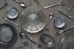 Vintage spoons, forks, knives and metal plates on a gray wooden background royalty free stock photography