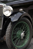 Vintage sports car detail. Full frame close-up of green wheel spokes and the front lamp of a restored black vintage sports car Royalty Free Stock Images