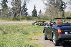 Vintage Sports Car picnic table. A Black 1975 MG Midget 1500 Vintage Sports Car in Tacoma, Washington parked by a picnic table royalty free stock photo