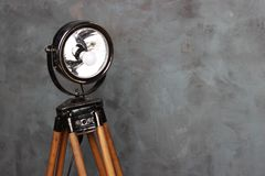 Searchlight on wooden legs. Vintage searchlight. Old floodlight. Vintage spotlight with white cement background. Searchlight on wooden legs. Vintage searchlight Royalty Free Stock Photos