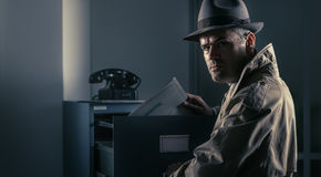 Vintage spy stealing files in the office Stock Image