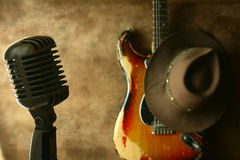 Vintage Stage. Vintage microphone and vintage sunburst strat with a cowboy hat Royalty Free Stock Images