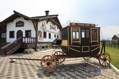 Vintage stagecoach and Restaurant Tavern Dillizhans. Tourist Complex Siberian Podvorye. Royalty Free Stock Images