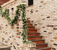 Vintage stair and orange brick wall. With a garland of green leaves Stock Photo