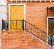 Vintage stairway and wooden door of brick building Stock Images