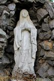 Vintage statue of a young virgin praying with a rosary hanging from her arms  with a rocks background Royalty Free Stock Image