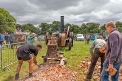 Vintage steam driven rock crusher. Men feeding old bricks into a vintage rock crushing machine powered by a steam traction engine through a huge drive belt Stock Images