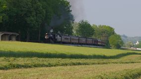 Vintage Steam Engine Train and Passenger Cars Arriving in Amish Countryside