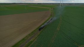 Vintage steam train. An aerial shot of a vintage steam train riding through a field with windmills stock video footage