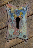 Vintage steel keyhole decorative element on weathered wooden sur Stock Images