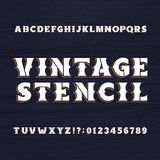 Vintage stencil typeface. Retro alphabet font on a wooden background. Royalty Free Stock Photography