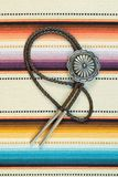 Vintage Silver Bolo Tie on colorful background. Vintage Sterling Silver Bolo Tie with Concho and Silver Tips on colorful southwestern hand woven fabric royalty free stock photos