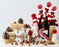 Vintage stile. Christmas card. Christmas decorations. Letters XMAS, gifts, knitwear, nuts and bottles of wine in knitted hats Royalty Free Stock Photo