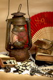 Vintage still life. Still life - oil lamp, old photos, antique domino and jewelry Stock Images