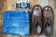 Vintage still life with aged boots. Shredded jeans, rasty keys and an old rangefinder camera Stock Images